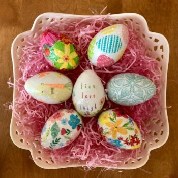 Seven Easter eggs laying on pink Easter grass in a white porcelain bowl
