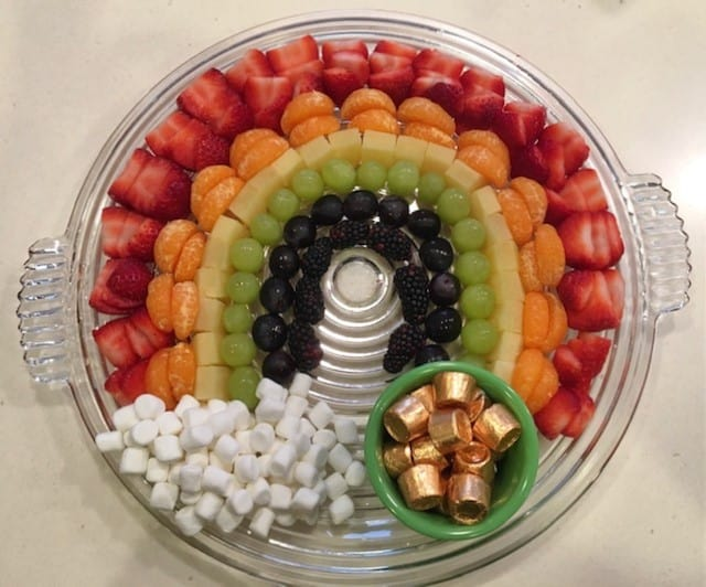 Fresh fruit made into a rainbow with mini marshmallow cloud and pot of gold candies