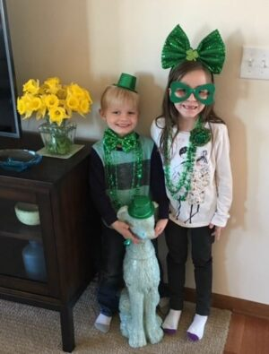 Little boy and girl with St. Patrick's Day hats, necklaces, glasses, bow tie, and ribbon